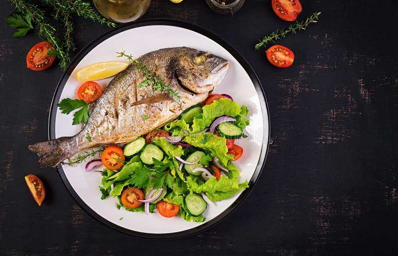 Το ψημένο dorado ψαριών με το λεμόνι και τα χορτάρια στο ψήσιμο φιλτράρουν στο σκοτεινό αγροτικό υπόβαθρο στοκ εικόνες