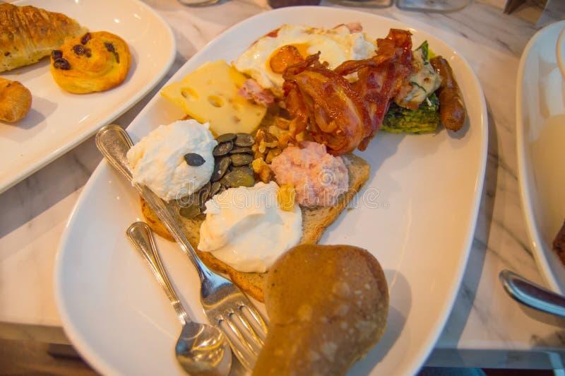 Το ψωμί, τα ανακατωμένα αυγά και το μπέϊκον στο πιάτο μετακινούν με το κουτάλι και τρώγοντας με ένα δίκρανο Παραδοσιακό εύγευστο  στοκ εικόνα