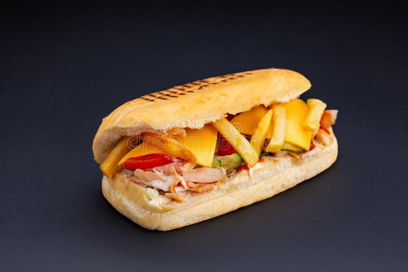 Το ψωμί Ciabatta γέμισε με το τυρί, το κρέας και τα λαχανικά στο σκοτεινό υπόβαθρο, την εκλεκτική εστίαση και το κενό διάστημα στοκ εικόνες