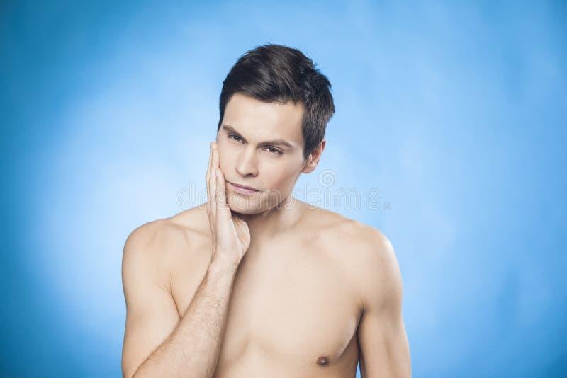 Το όμορφο άτομο γυμνοστήθων μπροστά από τον καθρέφτη που εξετάζει τον έλεγχο πηγουνιών του είναι αυτός καλά-που ξυρίζεται στοκ εικόνες