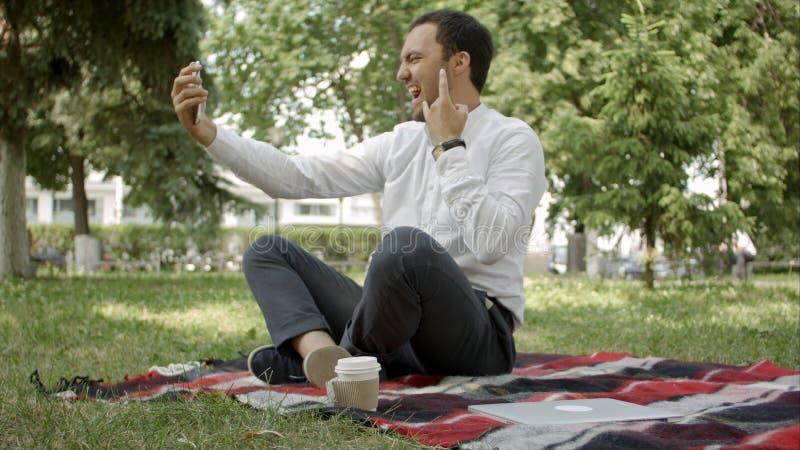 Το όμορφο άτομο κάνει selfie τη φωτογραφία στο πάρκο, καθμένος στη χλόη στοκ φωτογραφία με δικαίωμα ελεύθερης χρήσης