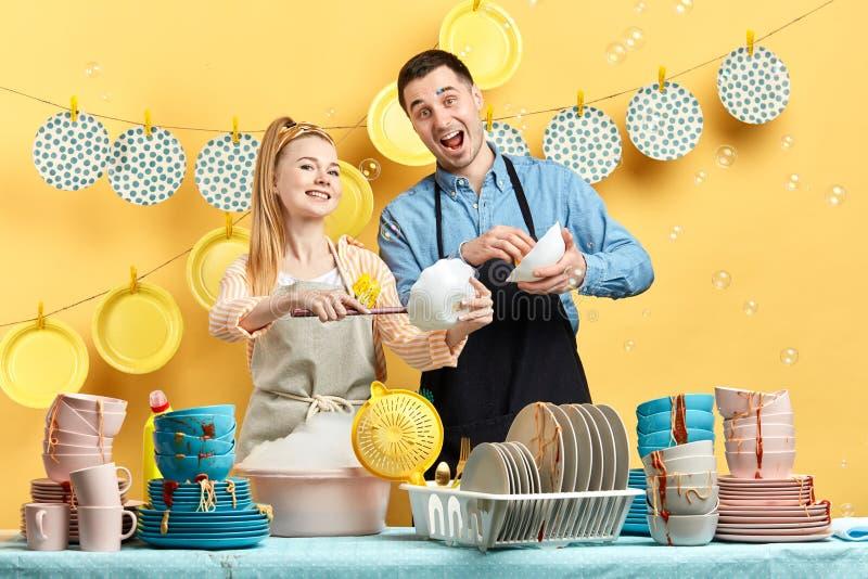 Το όμορφο άτομο τραγουδά ένα τραγούδι ξεσκονίζοντας τα πιάτα με τη σύζυγό του στοκ εικόνες