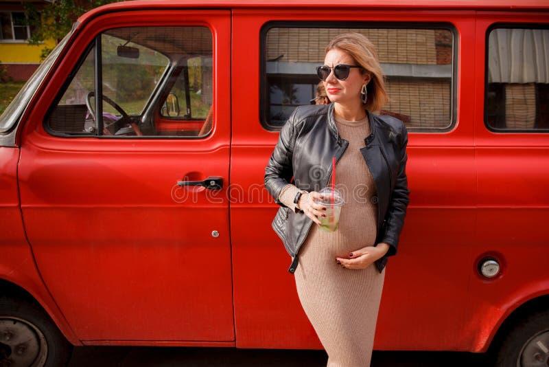 Το όμορφο έγκυο κορίτσι περπατά Το έγκυο κορίτσι στέκεται στην οδό και να ονειρευτεί Καθιερώνον τη μόδα κορίτσι εγκυμοσύνης Hipst στοκ εικόνες