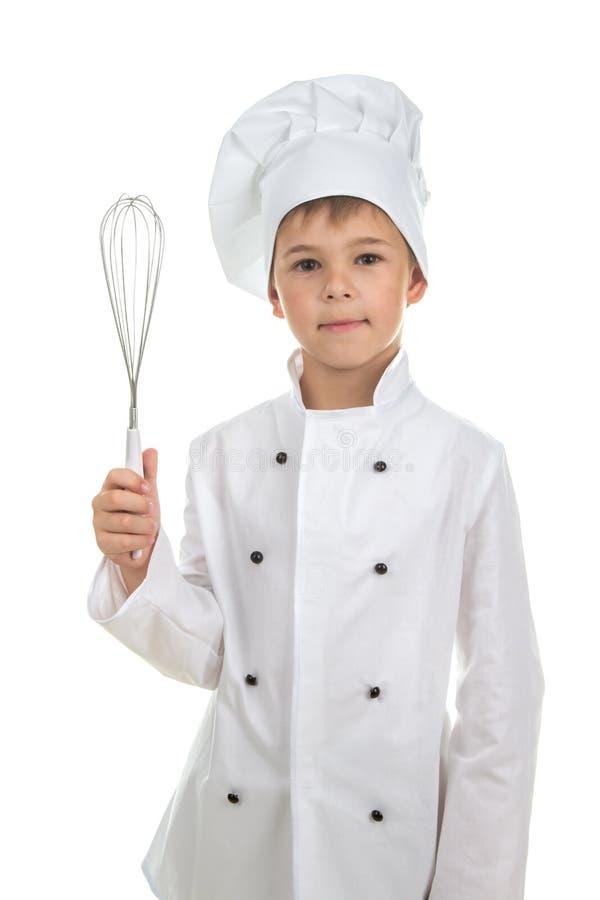 Το όμορφο αγόρι εφήβων στον αρχιμάγειρα ομοιόμορφο με ένα μαγείρεμα χτυπά ελαφρά, στο άσπρο υπόβαθρο στοκ εικόνες με δικαίωμα ελεύθερης χρήσης