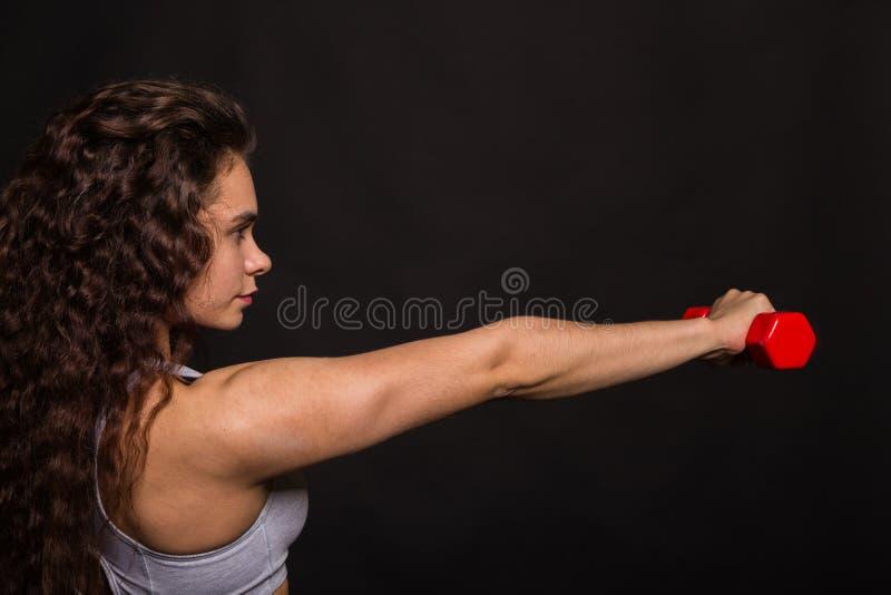 Το όμορφο αθλητικό κορίτσι σε ένα σκοτεινό υπόβαθρο στοκ εικόνα