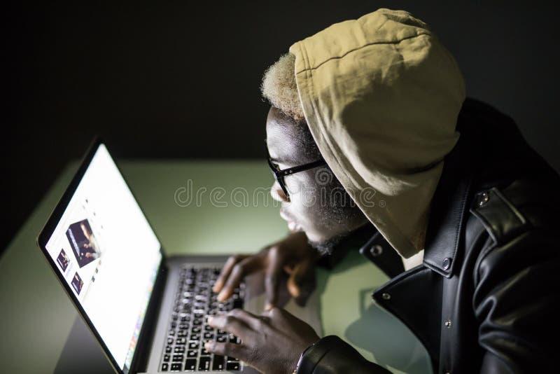 Το όμορφο αμερικανικό άτομο Afro που χρησιμοποιεί ένα lap-top κοιτάζει βιαστικά σε Διαδίκτυο μέχρι αργά τη νύχτα Παιχνίδια παιχνι στοκ φωτογραφίες με δικαίωμα ελεύθερης χρήσης