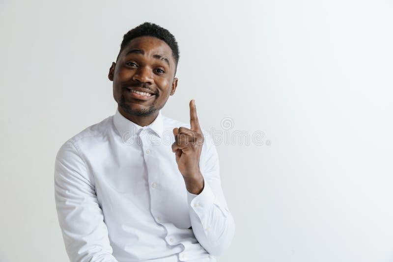 Το όμορφο αμερικανικό άτομο Afro στο κλασικό πουκάμισο χαμογελά, εξετάζει τη κάμερα και δείχνει μακριά στοκ εικόνες
