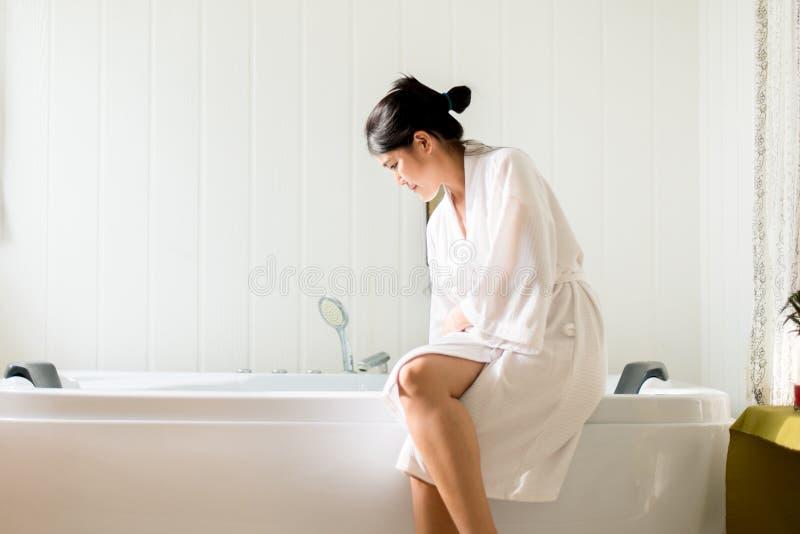 Το όμορφο ασιατικό θηλυκό που γεμίζει επάνω με το νερό και χαλαρώνει στην μπανιέρα στο ξενοδοχείο, ευτυχής και χαμογελώντας στοκ φωτογραφία με δικαίωμα ελεύθερης χρήσης