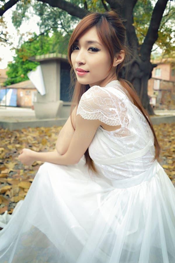 Το όμορφο ασιατικό κορίτσι έντυσε στο άσπρο φόρεμα στα φύλλα στοκ εικόνες