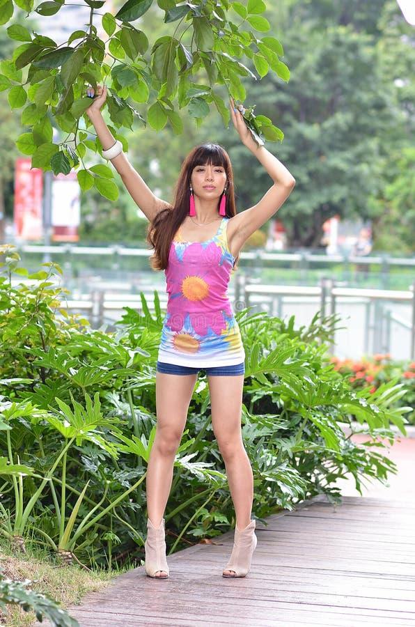 Το όμορφο ασιατικό κορίτσι παρουσιάζει νεολαία της στο πάρκο στοκ εικόνες