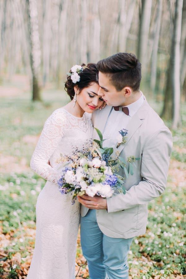 Το όμορφο γαμήλιο ζεύγος με τη νυφική ανθοδέσμη της άνοιξη ανθίζει στα χέρια στο πράσινο πάρκο στοκ εικόνες με δικαίωμα ελεύθερης χρήσης