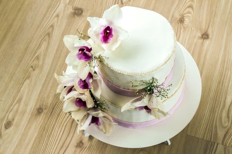 Το όμορφο γαμήλιο κέικ με τα λουλούδια, κλείνει επάνω του κέικ με το blurr στοκ φωτογραφία
