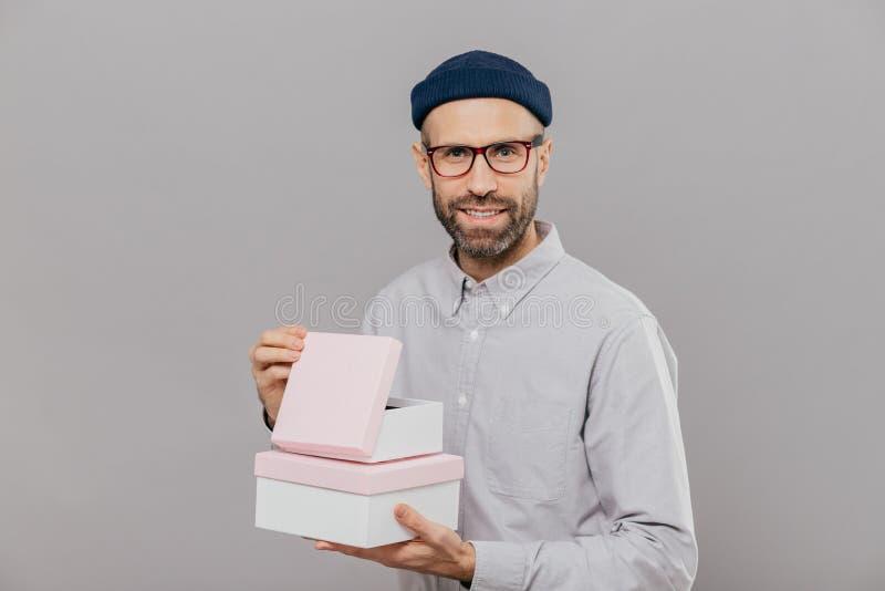 Το όμορφο ευρωπαϊκό άτομο με τις παχιές καλαμιές, ευχάριστο χαμόγελο, κρατά τα κιβώτια στα χέρια, ανοίγει το δώρο με την ευτυχία, στοκ φωτογραφία