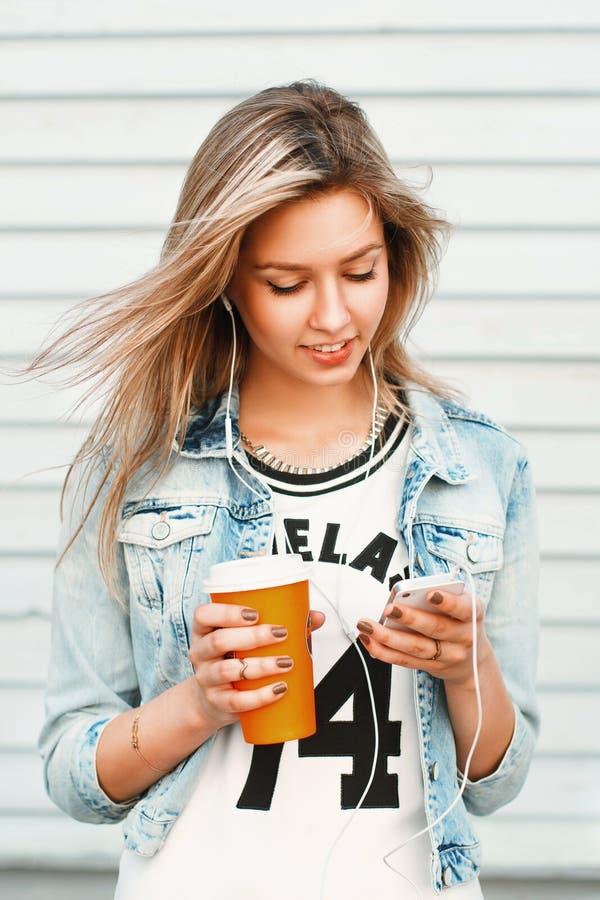 Το όμορφο ευτυχές κορίτσι hipster ακούει τη μουσική στο τηλέφωνο και το δ στοκ εικόνα με δικαίωμα ελεύθερης χρήσης