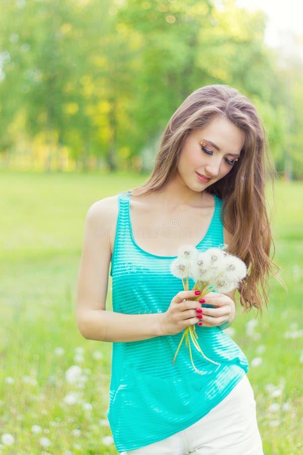 Το όμορφο ευτυχές χαμογελώντας κορίτσι με τις μακριές πικραλίδες στα χέρια των σορτς και μιας μπλούζας στηρίζεται στο πάρκο σε μι στοκ εικόνες