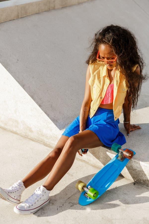 Το όμορφο εφηβικό μαύρο κορίτσι στην μπλε φούστα κάθεται με την πένα της lo στοκ εικόνες με δικαίωμα ελεύθερης χρήσης