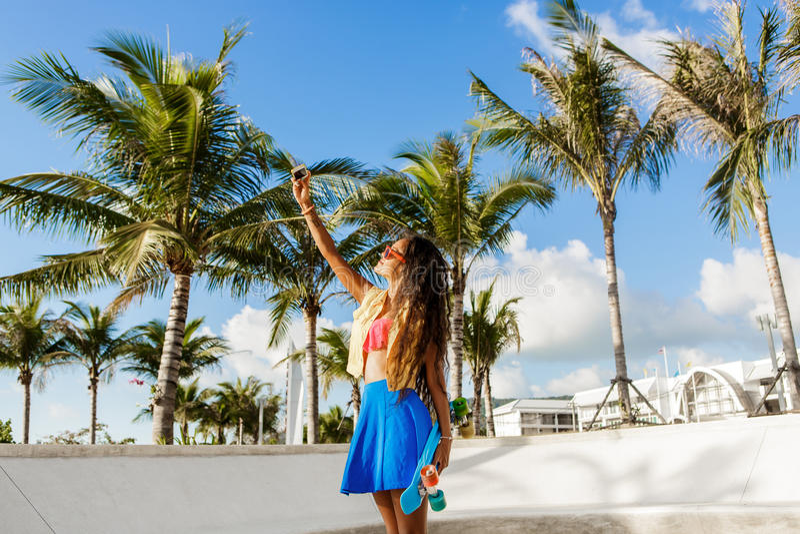 Το όμορφο εφηβικό μαύρο κορίτσι στην μπλε φούστα παίρνει selfie με την στοκ φωτογραφία με δικαίωμα ελεύθερης χρήσης