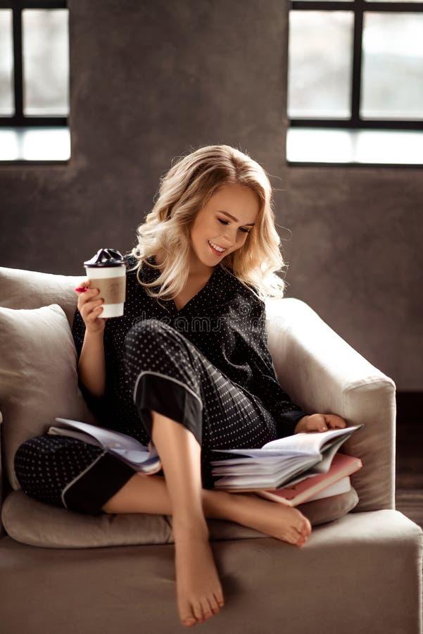 Το όμορφο εύθυμο νέο ξανθό θηλυκό στις πυτζάμες απολαμβάνει τον καφέ πρωινού, διαβάζει το βιβλίο όπως προετοιμάζεται για την παρο στοκ φωτογραφίες με δικαίωμα ελεύθερης χρήσης