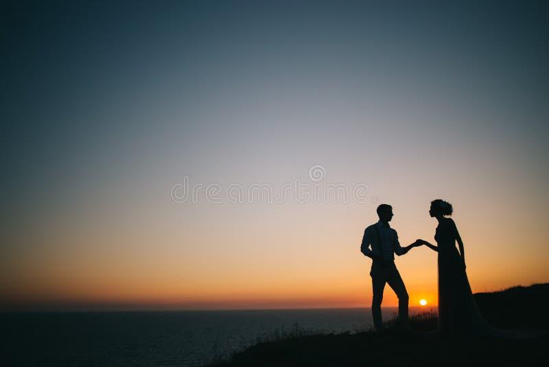 Το όμορφο ηλιοβασίλεμα εν πλω, ένας άνδρας και τα χέρια μιας γυναικών λαβής, εξετάζουν το ένα το άλλο, μια αγάπη στοκ φωτογραφία