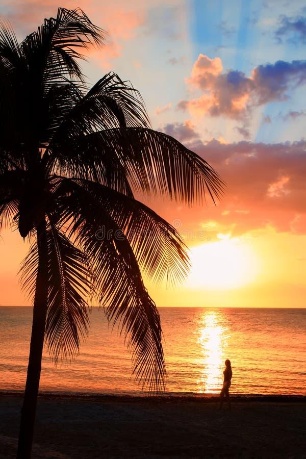 Το όμορφο ηλιοβασίλεμα στην παραλία, ήλιος πηγαίνει κάτω στη θάλασσα, σκιαγραφία γυναικών στο bayshore Ήρεμο περιβαλλοντικό, conc στοκ φωτογραφία