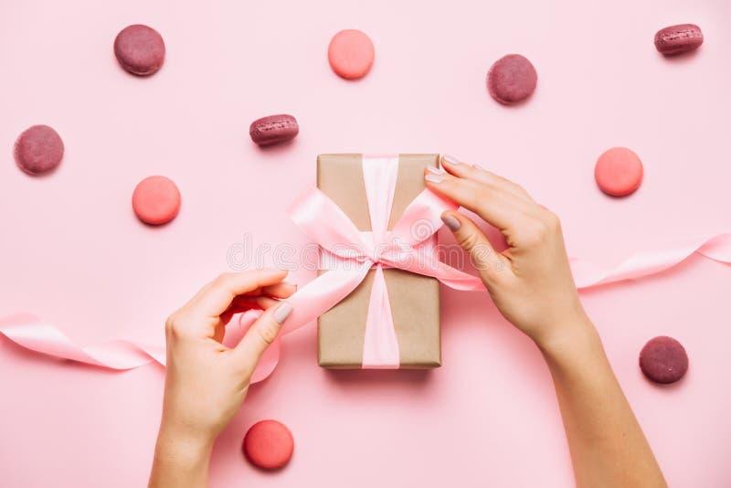 Το όμορφο θηλυκό μανικιούρ μόδας χεριών 6ος δένει ένα τόξο στο κιβώτιο δώρων στοκ φωτογραφία με δικαίωμα ελεύθερης χρήσης