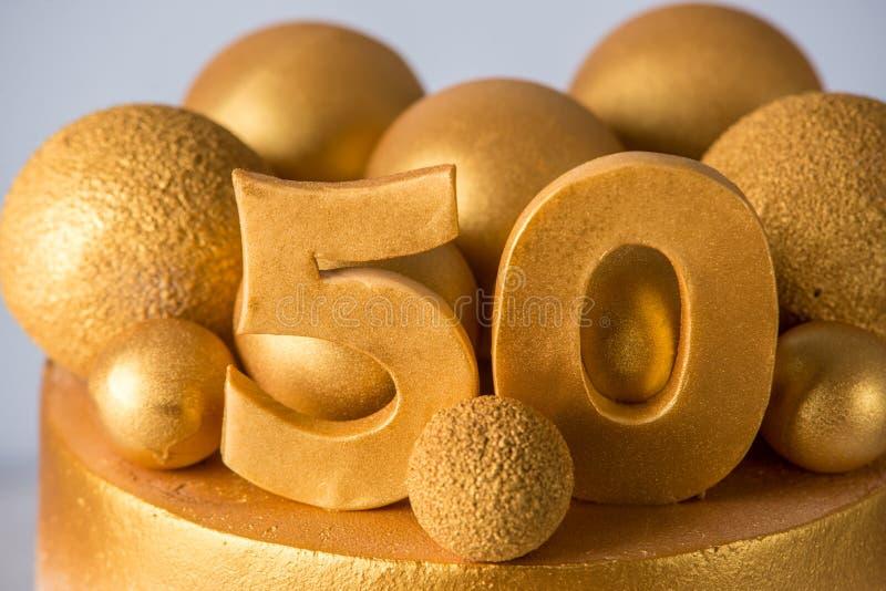 Το όμορφο κέικ για τη 50η επέτειο του γάμου διακόσμησε με τις χρυσά σφαίρες και τα δαχτυλίδια Έννοια των εορταστικών επιδορπίων στοκ φωτογραφία με δικαίωμα ελεύθερης χρήσης