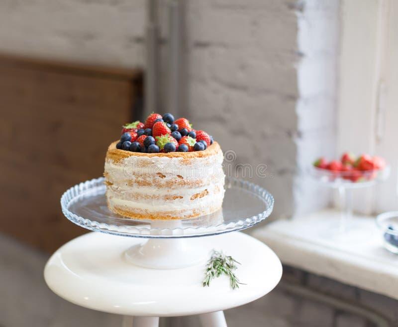Το όμορφο κέικ μπισκότων με την άσπρη κρέμα που διακοσμείται με τις φράουλες και τα βακκίνια σε ένα άσπρο βάθρο στέκεται στο παρά στοκ εικόνες