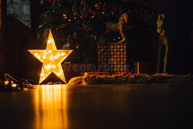 Το όμορφο καθιστικό Χριστουγέννων με το διακοσμημένα δέντρο, τα δώρα και την πυράκτωση ανάβει τη νύχτα στοκ φωτογραφία με δικαίωμα ελεύθερης χρήσης