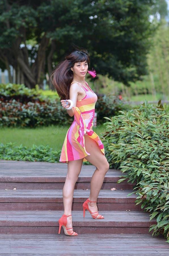 Το όμορφο και ασιατικό κορίτσι φύλων παρουσιάζει νεολαία της στο πάρκο στοκ εικόνες