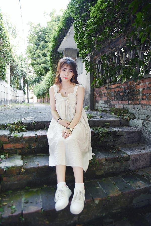 Το όμορφο και καλό ασιατικό κορίτσι παρουσιάζει νεολαία της στο πάρκο στοκ εικόνα