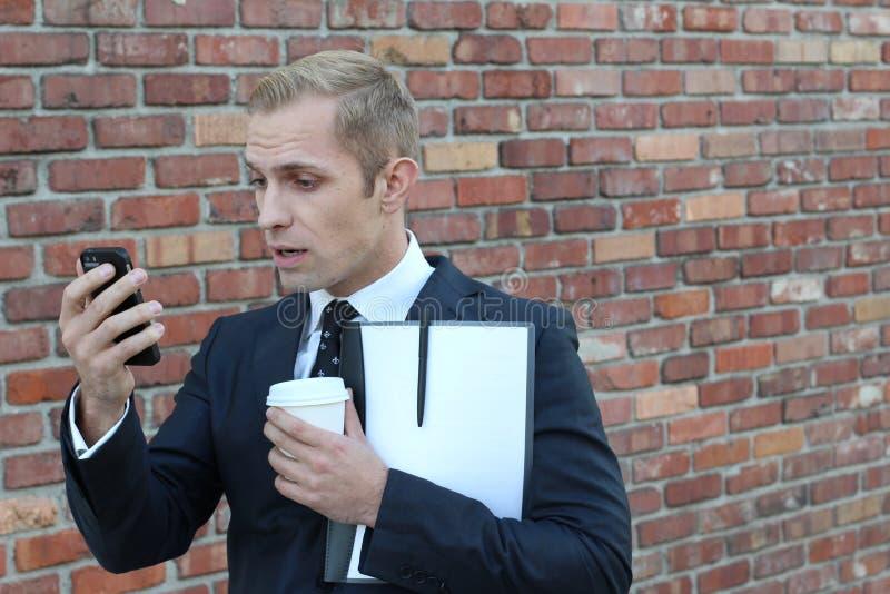 Το όμορφο καυκάσιο άτομο που εξετάζει το τηλέφωνο καταπλήσσει το πορτρέτο που απομονώνεται στο τούβλινο αστικό υπόβαθρο τοίχων στοκ φωτογραφία με δικαίωμα ελεύθερης χρήσης