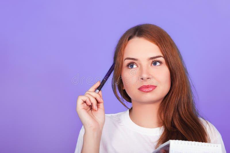 Το όμορφο κοκκινομάλλες κορίτσι με τα μπλε μάτια σε μια άσπρη μπλούζα σκέφτεται τι για να γράψει σε ένα σημειωματάριο Κινηματογρά στοκ εικόνες