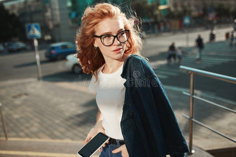 Το όμορφο κοκκινομάλλες κορίτσι στέκεται στην οδό στο υπόβαθρο της πόλης και την τοποθέτηση στη κάμερα Το κορίτσι φορά μια μπλούζ στοκ εικόνα με δικαίωμα ελεύθερης χρήσης