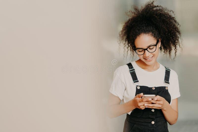 Το όμορφο κορίτσι αφροαμερικάνων στο μοντέρνο ιματισμό, κινητό τηλέφωνο χρήσεων για την αποστολή των μηνυμάτων κειμένου, σύνδεσε  στοκ φωτογραφίες με δικαίωμα ελεύθερης χρήσης