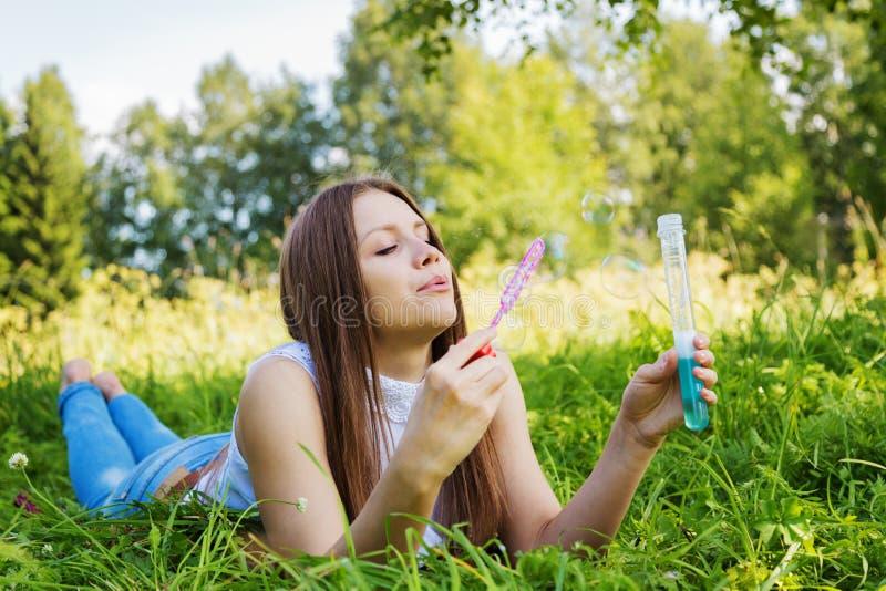 Το όμορφο κορίτσι βρίσκεται στο λιβάδι και τις φυσώντας φυσαλίδες σαπουνιών στοκ φωτογραφίες