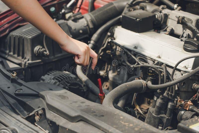 Το όμορφο κορίτσι δίνει ανοικτός τη φούστα αυτοκινήτων για να ελέγξει το επίπεδο πετρελαίου του αυτοκινήτου Η έννοια του ταξιδιού στοκ εικόνες