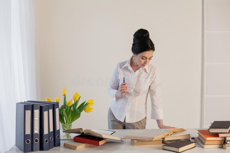 Το όμορφο κορίτσι διαβάζει τα βιβλία στον πίνακα προετοιμαμένος για το διαγωνισμό στοκ εικόνες