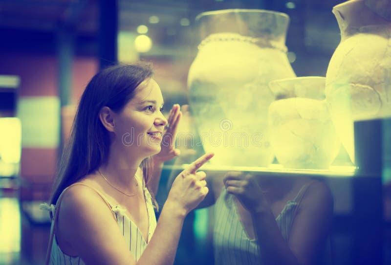 Το όμορφο κορίτσι εξετάζει τα εκθέματα στο μουσείο στοκ εικόνες