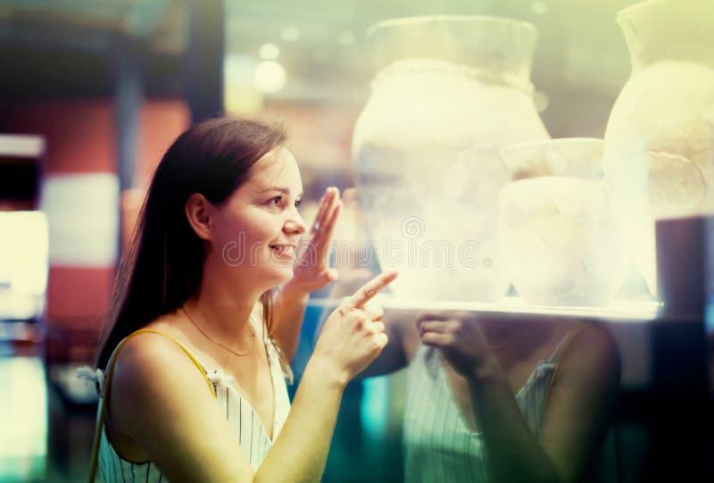 Το όμορφο κορίτσι εξετάζει τα εκθέματα στο μουσείο στοκ φωτογραφίες με δικαίωμα ελεύθερης χρήσης