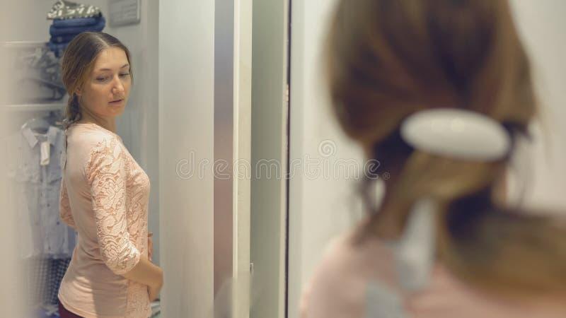 Το όμορφο κορίτσι εξετάζει την αντανάκλασή της στον καθρέφτη προσπαθώντας στα ενδύματα στο κατάστημα μόδας ψωνίζοντας στοκ φωτογραφία με δικαίωμα ελεύθερης χρήσης