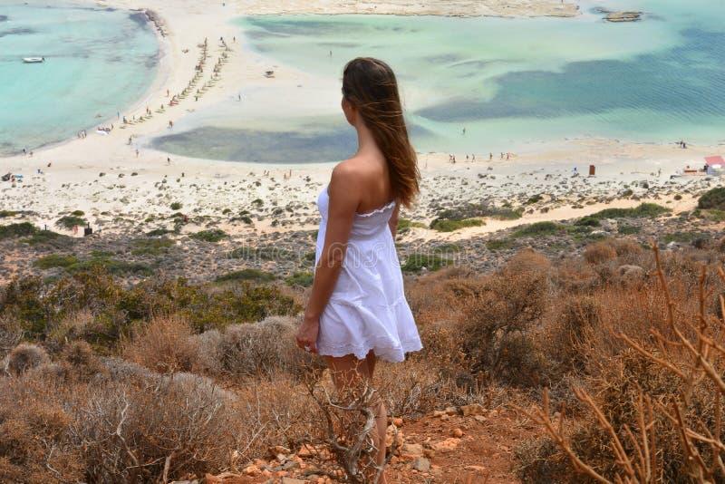 Το όμορφο κορίτσι εξετάζει τη λιμνοθάλασσα με μια διαφανή και σαφή θάλασσα στοκ εικόνα