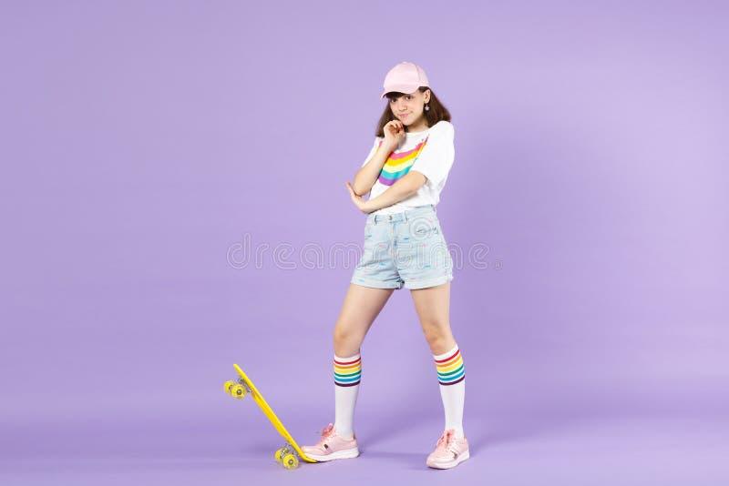 Το όμορφο κορίτσι εφήβων στα ζωηρά ενδύματα που στέκονται με κίτρινο skateboard, έβαλε το στήριγμα χεριών επάνω στο πηγούνι που α στοκ εικόνες