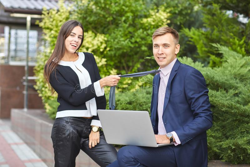 Το όμορφο κορίτσι και ο όμορφος τύπος λειτουργούν στο πάρκο σε έναν υπολογιστή σε ένα φυσικό υπόβαθρο στοκ φωτογραφία με δικαίωμα ελεύθερης χρήσης