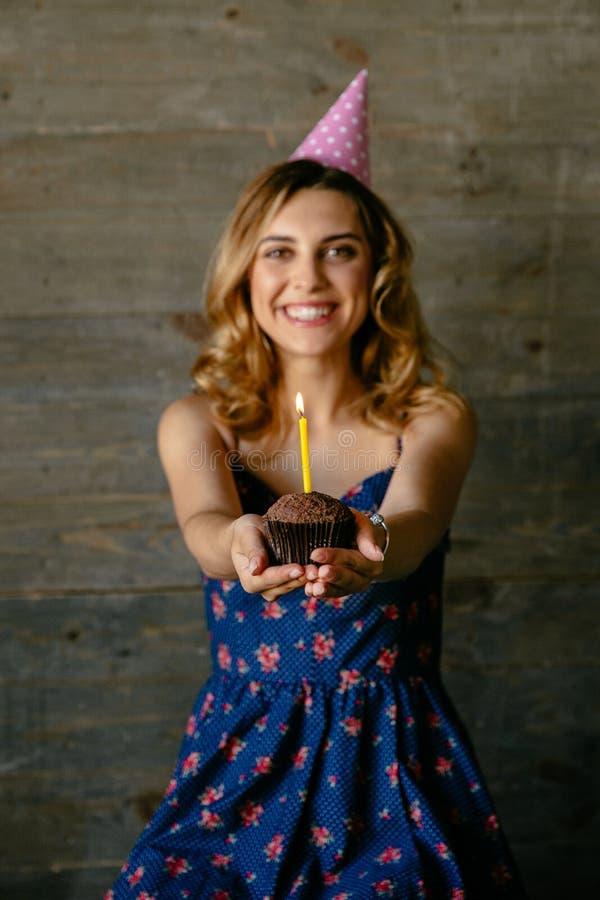 Το όμορφο κορίτσι κρατά μια σοκολάτα cupcake με το κερί στοκ φωτογραφία με δικαίωμα ελεύθερης χρήσης