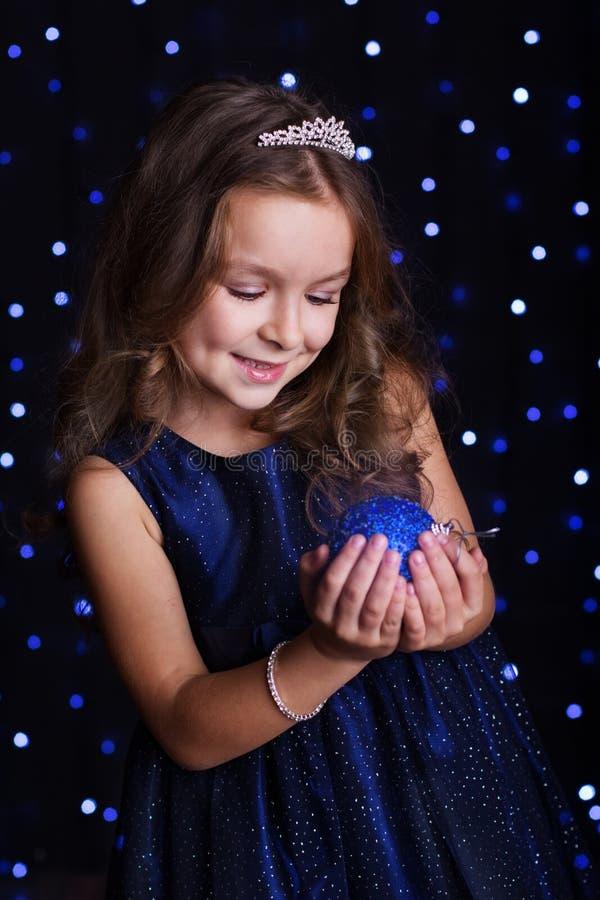 Το όμορφο κορίτσι κρατά την μπλε σφαίρα Χριστουγέννων στοκ εικόνα