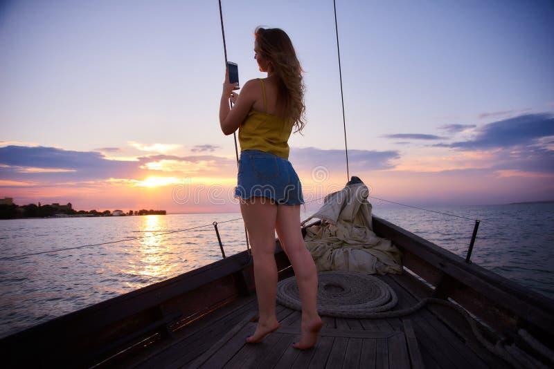 Το όμορφο κορίτσι με μακρυμάλλη συναντά την αυγή Πλέοντας βάρκα στη θάλασσα στο ηλιοβασίλεμα στοκ εικόνες