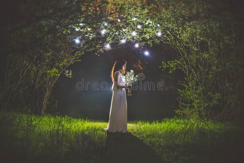 Το όμορφο κορίτσι με την ανθοδέσμη παραδίδει μέσα τον κήπο βραδιού στοκ εικόνες με δικαίωμα ελεύθερης χρήσης