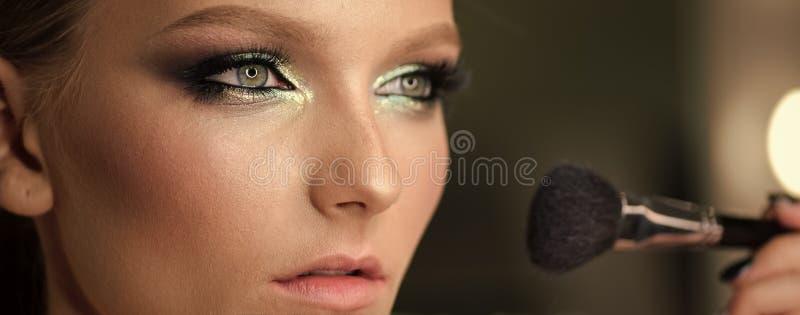 Το όμορφο κορίτσι με την καλλυντική βούρτσα σκονών για αποτελεί makeup Αποτελέστε να ισχύσει για το τέλειο δέρμα στοκ φωτογραφίες