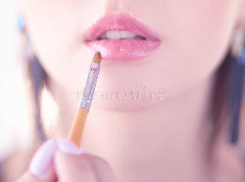 Το όμορφο κορίτσι με την καλλυντική βούρτσα σκονών για αποτελεί makeup Σύνθεση που ισχύει για το τέλειο δέρμα στοκ φωτογραφίες