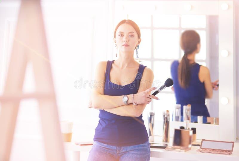 Το όμορφο κορίτσι με την καλλυντική βούρτσα σκονών για αποτελεί makeup Σύνθεση που ισχύει για το τέλειο δέρμα στοκ εικόνες